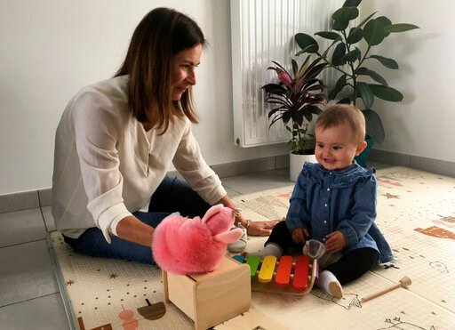 (AP Photo/Catherine Gaschka). Sandrine Rudnicki, a 38 years old single woman smiles to her 10-month old daughter Emilia who was conceived through in-vitro fertilization, Monday Oct.14, 2019 in Saint-Pryve-Saint-Mesmin, near Orleans, France. France's lo...