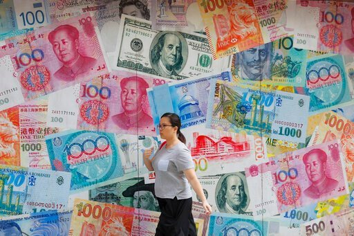 (AP Photo/Kin Cheung, File). FILE - In this Aug. 6, 2019, file photo, a woman walks by a money exchange shop decorated with different countries currency banknotes at Central, a business district in Hong Kong. The IMF's latest World Economic Outlook com...