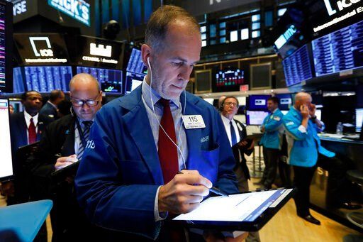 (AP Photo/Richard Drew, File). FILE - In this Oct. 8, 2019, file photo trader Mark Puetzer, center, works on the floor of the New York Stock Exchange. The U.S. stock market opens at 9:30 a.m. EDT on Tuesday, Oct. 15.