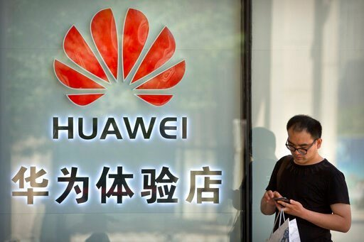 (AP Photo/Mark Schiefelbein, File). FILE - In this May 29, 2019, file photo, a man uses his smartphone outside of a shop selling Huawei products at a shopping mall in Beijing. The New York Times reports the Trump administration plans to issue licenses ...