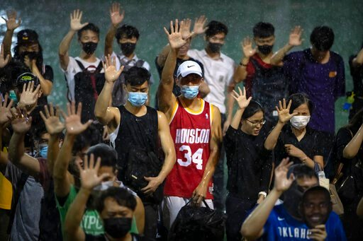 (AP Photo/Mark Schiefelbein). A demonstrator wearing Houston Rockets jersey holds up his hand with fellow demonstrators during a rally at the Southorn Playground in Hong Kong, Tuesday, Oct. 15, 2019. Protesters in Hong Kong have thrown basketballs at a...