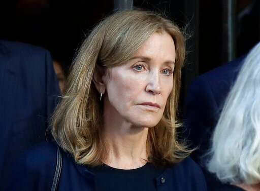 (AP Photo/Elise Amendola, File). FILE - This Sept. 13, 2019 file photo shows actress Felicity Huffman leaving federal court after her sentencing in a nationwide college admissions bribery scandal in Boston. A representative for Huffman says she reporte...