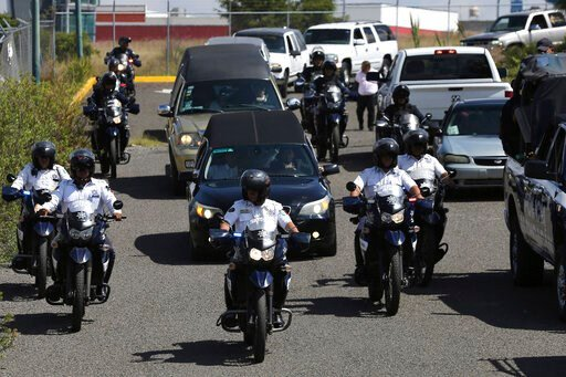 (AP Photo/Marco Ugarte). Police escort a caravan of funeral vehicles transporting the bodies of Mexican police officers killed in an apparent cartel ambush, in Morelia, Mexico, Tuesday, Oct. 15, 2019. The families of the 13 slain police officers gather...