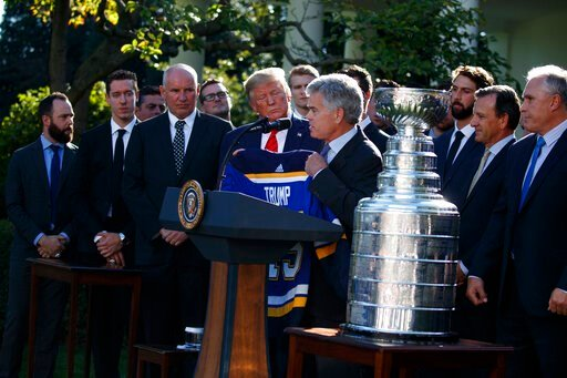 (AP Photo/Evan Vucci). President Donald Trump is presented a team jersey by St. Louis Blues owner Tom Stillman during an event to honor the 2019 Stanley Cup Champion St. Louis Blues, in the Rose Garden of the White House, Tuesday, Oct. 15, 2019, in Was...