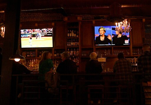 (AP Photo/Nick Wass). Patrons at the Hawk 'n' Dove sit in front of television screens televising Game 4 of the NLCS between Washington Nationals and the St. Louis Cardinals and a debate by Democratic presidential candidates, Tuesday, Oct. 15, 2019, in ...