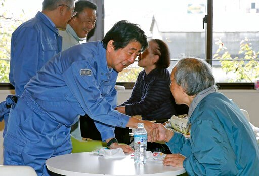 (Shohei Miyano/Kyodo News via AP). Japan's Prime Minister Shinzo Abe, front left, visits a shelter for people affected by Typhoon Hagibis, in Motomiya, Fukushima prefecture, Japan Thursday, Oct. 17, 2019. The typhoon hit Japan on Saturday with historic...