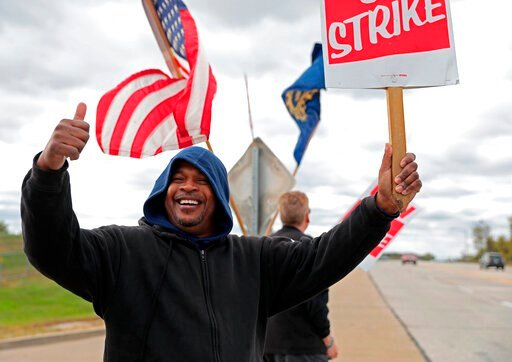 (Cristina M. Fletes/St. Louis Post-Dispatch via AP). Bill Jackson, of St. Louis, gives a thumbs up to drivers that wave or honk as United Auto Workers outside the GM Wentzville Assembly Center in Wentzville, Mo.,  Wednesday, Oct. 16, 2019. UAW workers ...