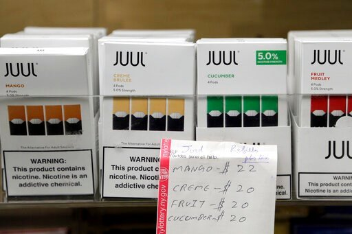 (AP Photo/Seth Wenig). FILE - In this Thursday, Dec. 20, 2018 file photo, Juul products are displayed at a smoke shop in New York. On Thursday, Oct. 17, 2019, the company announced it will voluntarily stop selling its fruit and dessert-flavored vaping ...
