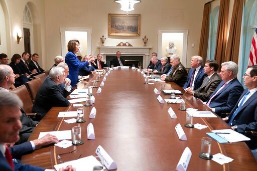 (Official White House Photo by Shealah Craighead via AP). In this photo released by the White House, President Donald Trump, center right, meets with House Speaker Nancy Pelosi, standing left, Congressional leadership and others, Wednesday, Oct. 16, 20...