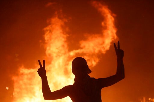 (AP Photo/Hassan Ammar). An anti-government protester makes victory signs in front a fire set to block a road during a demonstration in Beirut, Lebanon, Thursday, Oct. 17, 2019. Scores of people are protesting in Beirut and other parts of Lebanon over ...