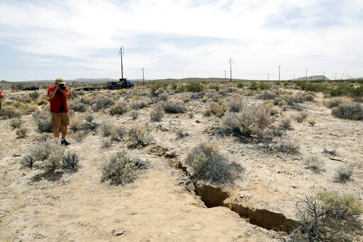 (AP Photo/Marcio Jose Sanchez, File). FILE - In this July 7, 2019 file photo, a visitor takes a photo of a crack in the ground following recent earthquakes near Ridgecrest, Calif. Scientists say the earthquakes that hammered the Southern California des...