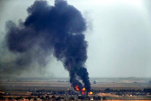 (AP Photo/Cavit Ozgul). In this photo taken from the Turkish side of the border between Turkey and Syria, in Ceylanpinar, Sanliurfa province, southeastern Turkey, flames and smoke billow from a fire on a target in Ras al-Ayn, Syria, caused by shelling ...