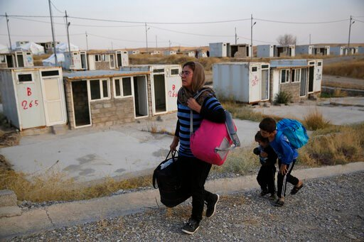 (AP Photo/Hussein Malla). FILE - In this Oct. 17, 2019 file photo, Salwa Hanna with her children, who are newly displaced by the Turkish military operation in northeastern Syria, carry their belongings after they arrive at the Bardarash refugee camp, n...