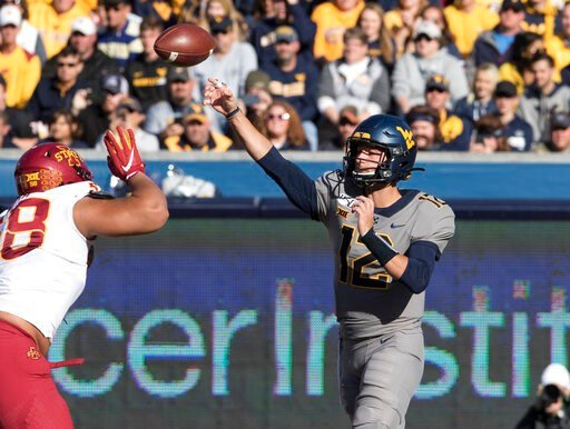 (AP Photo/Raymond Thompson). West Virginia quarterback Austin Kendall (12) attempts a pass during the first half of an NCAA college football game against Iowa State Saturday, Oct. 12, 2019, in Morgantown, W.Va.