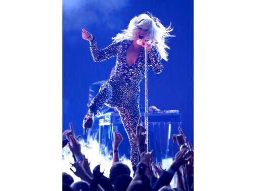 (Photo by Matt Sayles/Invision/AP, File). FILE - This Feb. 10, 2019 file photo shows Lady Gaga performing at the Grammy Awards in Los Angeles. Lady Gaga is recovering after falling off stage while dancing with a fan at a concert. During her Las Vegas s...
