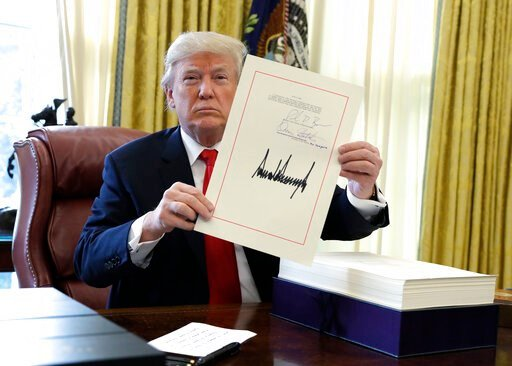 (AP Photo/Evan Vucci, File). FILE - In this Dec. 22, 2017, file photo, President Donald Trump displays the $1.5 trillion tax overhaul package he signed in the Oval Office of the White House in Washington. Trump is now three for three. Each year of his ...