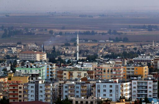 (AP Photo/Lefteris Pitarakis). In this photo taken from the Turkish side of the border between Turkey and Syria, in Ceylanpinar, Sanliurfa province, southeastern Turkey, a new of Ras al-Ayn, Syria, Friday, Oct. 18, 2019. Fighting broke out in the morni...