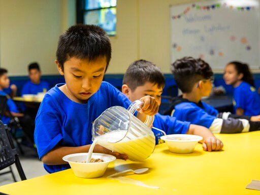 (Ashlee Rezin Garcia /Chicago Sun-Times via AP). A student pours milk on his cereal  as Mayor Lori Lightfoot passes out breakfast to Chicago Public Schools students at a contingency site, Gads Hill Center Friday, Oct. 18, 2019. Striking Chicago teacher...