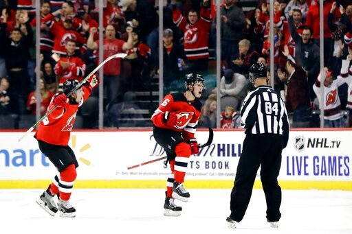 (AP Photo/Frank Franklin II). New Jersey Devils' Jack Hughes, center, celebrates with teammate Sami Vatanen, left, after scoring his first career NHL goal during the first period of a hockey game against the Vancouver Canucks, Saturday, Oct. 19, 2019, ...