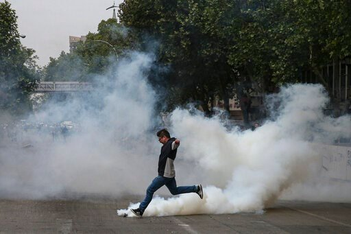 (AP Photo/Esteban Felix). A protester kicks a tear gas canister launched by police during a protest in Santiago, Chile, Saturday, Oct. 19, 2019. The protests started on Friday afternoon when high school students flooded subway stations, jumping turnsti...