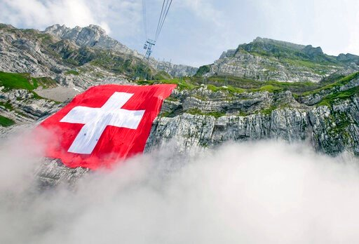 (Ennio Leanza/Keystone via AP). File---Picture taken July 31, 2009 shows the world largest Swiss flag hanging at the rock face of the mountain Saentis in Schwaegalp, Switzerland, The flag measures 120 meters square and is believed to be the world secon...