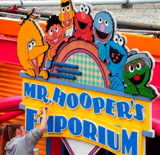 (Harry Sircely/Bucks County Courier Times via AP, File). FILE - In this May 4, 2005, file photo, Tessa Meier puts some new paint on the sign outside Mr. Hooper's Emporium to get ready for opening day at Sesame Place in Langhorne, Pa. Officials with Sea...