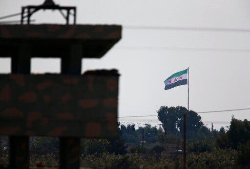(AP Photo/Lefteris Pitarakis). Syria's opposition flag flies on a pole in Tal Abyad, Syria, as seen from the town of Akcakale, Sanliurfa province, southeastern Turkey, Monday, Oct. 21, 2019. Turkey's President Recep Tayyip Erdogan is scheduled to meet ...