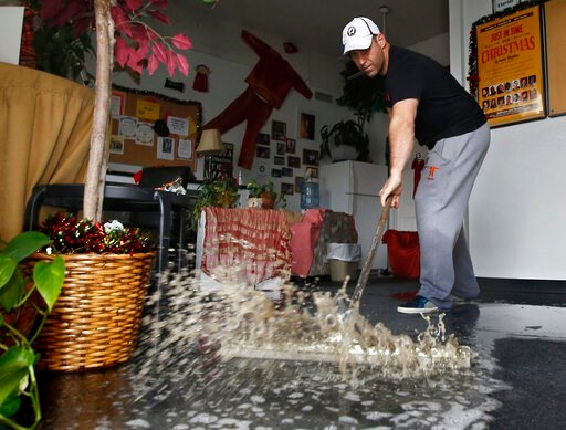 (AP Photo/Rich Pedroncelli, File). FILE - In this Jan. 5, 2016, file photo, Chris Lene sweeps water out of one of the businesses in the building he owns that was flooded by rainwater in Sacramento, Calif. Climate change is making stronger El Ninos, whi...