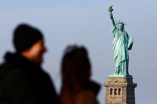 (AP Photo/Mark Lennihan, File). FILE - In this Jan. 21, 2018, file photo, tourists ride the Staten Island Ferry to get a view of the Statue of Liberty in New York. A new poll from The Associated Press-NORC Center for Public Affairs Research shows major...