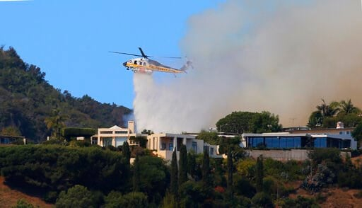 (AP Photo/Reed Saxon). A helicopter makes a water drop as flames threaten homes on a ridgeline as a wildfire threatens homes in the Pacific Palisades area of Los Angeles, Monday, Oct. 21, 2019.