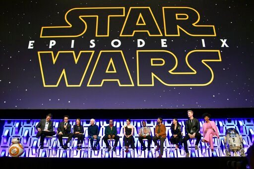 (Photo by Rob Grabowski/Invision/AP, File). FILE - In this April 12, 2019, file photo, Stephen Colbert, from left, J.J. Abrams, Kathleen Kennedy, Anthony Daniels, Billy Dee Williams, Daisy Ridley, John Boyega, Oscar Isaac, Kelly Marie Tran, Joonas Suot...