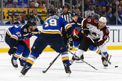 (AP Photo/Scott Kane). Colorado Avalanche's Tyson Jost, right, looks to get the puck past St. Louis Blues' Jay Bouwmeester (19) and Alex Pietrangelo (27) during the second period of an NHL hockey game Monday, Oct. 21, 2019, in St. Louis.