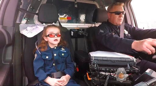 (Denver Police Department/The Denver Post via AP). In this image made from April 2017 video provided by the Denver Police Department, Olivia Gant, who was 6 years old at the time, rides with Cpt. Tim Scudder on a call in Denver. On Monday, Oct. 21, 201...
