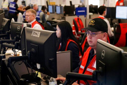 (AP Photo/Jeff Chiu, File). FILE - In this Oct. 10, 2019, file photo, Pacific Gas & Electric employees work in the PG&E Emergency Operations Center in San Francisco. Authorities say power outages have started Wednesday, Oct. 23, 2019, in Northe...