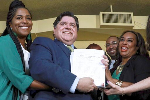 (AP Photo/Amr Alfiky File). FILE - In this June 25, 2019 file photo, Gov. J. B. Pritzker holds a bill that legalizes adult-use cannabis in the state of Illinois accompanied by state Rep. Kelly Cassidy, left, and state Sen. Toi Hutchinson, right, in Chi...