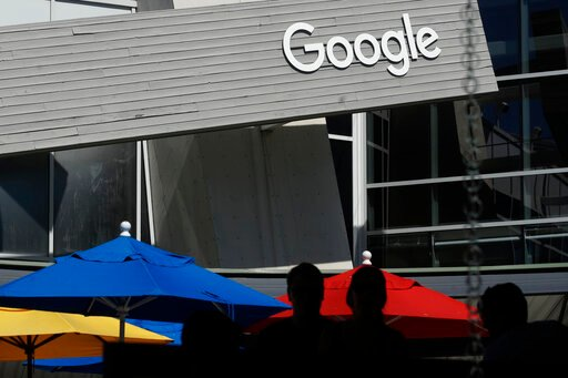 (AP Photo/Jeff Chiu, File). FILE - In this Sept. 24, 2019, file photo people walk by a Google sign on the campus in Mountain View, Calif. Alphabet's board of directors is investigating claims of sexual misconduct made against executives and how the com...