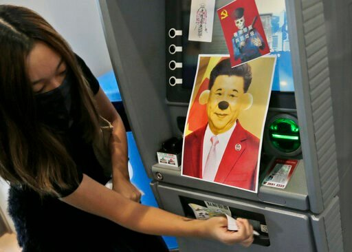 (AP Photo/Dita Alangkara). A protester attaches stickers and a defaced portrait of Chinese President Xi Jinping on a Bank of China's ATM machine during an anti-government rally at Hong Kong University of Science and Technology in Hong Kong, Thursday, N...