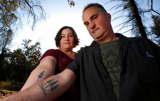 (AP Photo/Rich Pedroncelli). In this Thursday, Oct. 17, 2019, photo, Laura and Chris Smith display their Paradise tattoos they had done to show support for their former community during a visit to Paradise, Calif. The Smiths are now living in a small a...