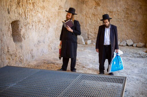 (AP Photo/Ariel Schalit). In this Thursday, Oct. 31, 2019 photo, ultra-Orthodox Jews pray in the Tomb of the Kings, a large underground burial complex dating to the first century BC, in east Jerusalem neighborhood of Sheikh Jarrah. After several aborte...