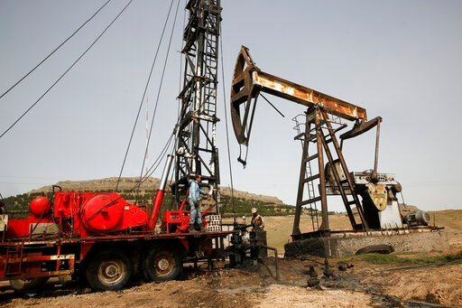 (AP Photo/Hussein Malla, File). FILE - This March 27, 2018 file photo shows Syrian workers fixing pipes of an oil well at an oil field controlled by a U.S-backed Kurdish group, in Rmeilan, Hassakeh province, Syria. President Donald Trump's decision to ...