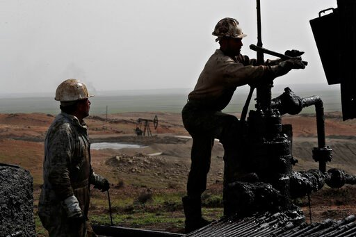 (AP Photo/Hussein Malla, File). FILE - This March 27, 2018 file photo, shows Syrian workers fixing pipes of an oil well at an oil field controlled by a U.S-backed Kurdish group, in Rmeilan, Hassakeh province, Syria. President Donald Trump's decision to...