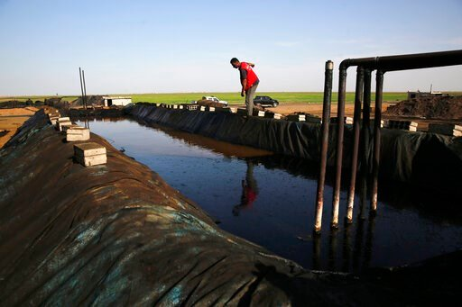 (AP Photo/Hussein Malla, File). FILE - In this April 6, 2018 file photo, shows a former farmer working at a primitive refinery making crude oil into diesel and other products, in a village controlled by a U.S-backed Kurdish group, in Rmeilan, Hassakeh ...