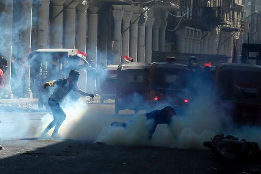 (AP Photo/Hadi Mizban). Iraqi riot police fire tear gas to disperse anti-government protesters during ongoing protests in Baghdad, Iraq, Friday, Nov. 8, 2019.
