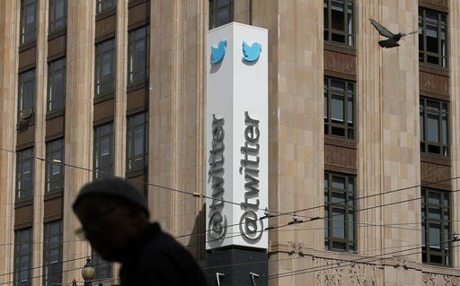 (AP Photo/Jeff Chiu, File). FILE - In this July 9, 2019, file photo a pedestrian walks across the street from the Twitter office building in San Francisco. A complaint unsealed in a federal court detailed a coordinated effort by Saudi officials to recr...