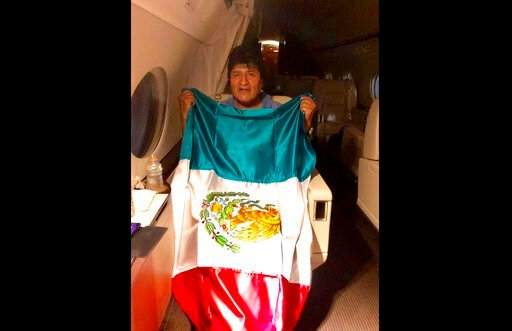(Mexico's Foreign Minister via AP). This photo released by by Mexico's Foreign Minister Marcelo Ebrard shows Bolivia's former President Evo Morales holding a Mexican flag aboard a Mexican Air Force aircraft, Monday, Nov. 11, 2019. Morales has been gran...