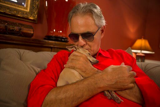 """(AP Photo/Ellis Rua). This Nov. 8, 2019 photo shows Italian tenor Andrea Bocelli with his dog Katarina during an interview at his home in North Miami, Fla. Bocelli is defending opera legend Placido Domingo and calling it """"absurd"""" that opera houses have..."""