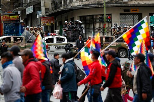 (AP Photo/Natacha Pisarenko). Police patrol on the sidelines of a march by supporters of former President Evo Morales, arriving from El Alto and entering La Paz, Bolivia, Tuesday, Nov. 12, 2019. Former President Evo Morales, who transformed Bolivia as ...