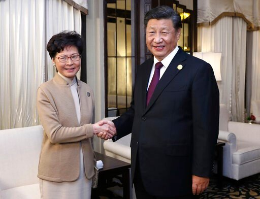 (Ju Peng/Xinhua via AP, File). FILE - In this Nov. 4, 2019, file photo released by China's Xinhua News Agency, Chinese President Xi Jinping, right, poses with Hong Kong Chief Executive Carrie Lam for a photo during a meeting in Shanghai, China. A sharp...