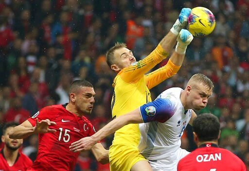 (AP Photo). Turkey's goalkeeper Mert Gunok, center, hits the ball by his teammate Merih Demiral, left, and Iceland's Kolbeinn Sigthorsson, right, during the Euro 2020 Group H qualifying soccer match between Turkey and Iceland in Istanbul, Thursday, Nov...