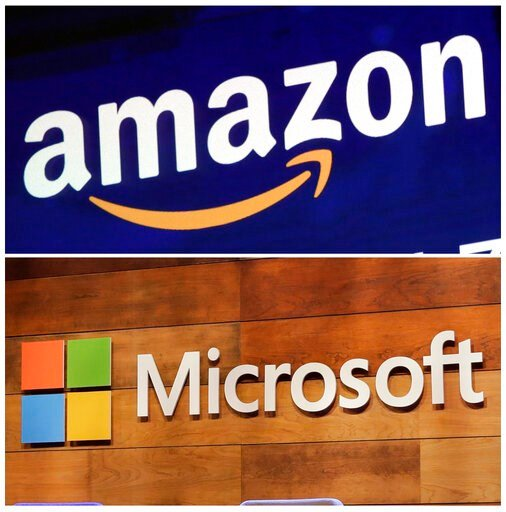 """(AP Photo/Richard Drew and Ted S. Warren, File). FILE - This combination of file photos shows the logos for Amazon, top, and Microsoft. . Amazon is protesting the Pentagon's decision to award a huge cloud-computing contract to Microsoft, citing """"unmist..."""